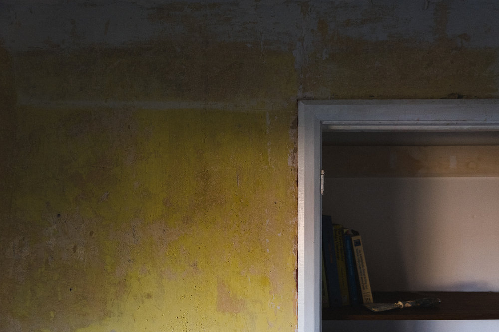 Peeling yellow paint on the walls inside a home
