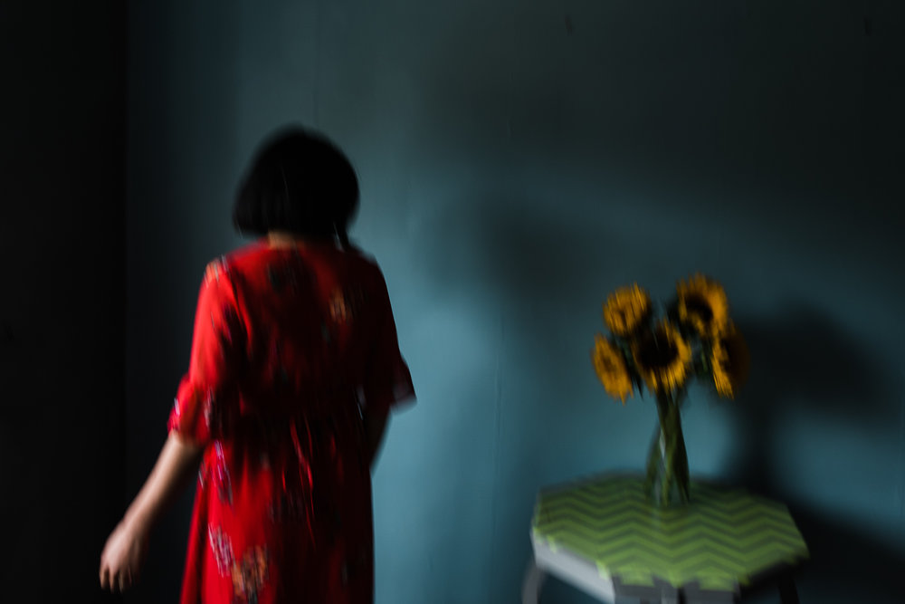 Artist stands by a green table with a vase of sunflowers on the