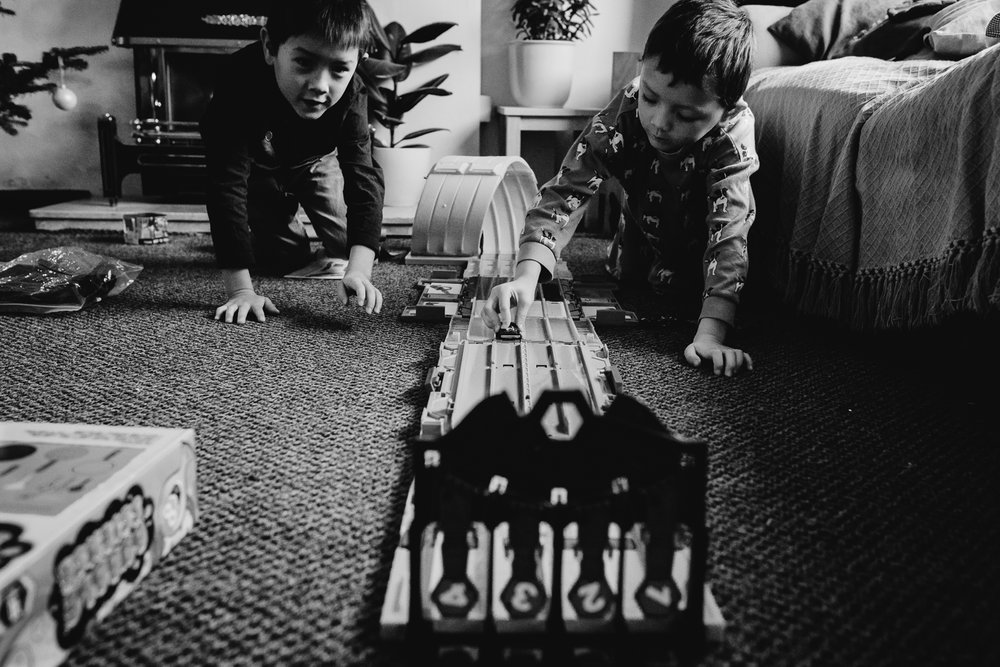 Black and white photograph of two brothers playing with their ho
