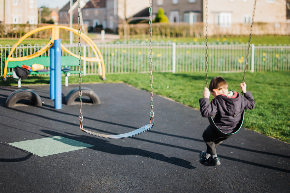 Boy sitting on a swing in the park with his long shadow in front