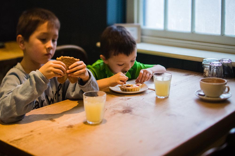 Children sitting inside Tom's Cakes cafe eating cake at the tabl