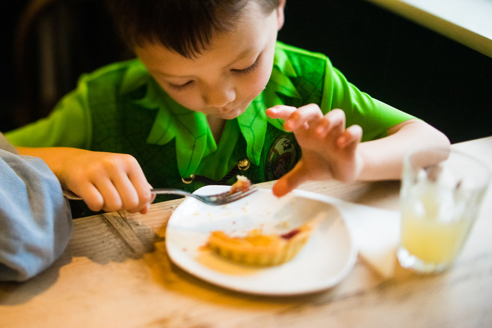 Boy eating his bakewell tart at Tom's Cakes cafe in St Ives, Cam