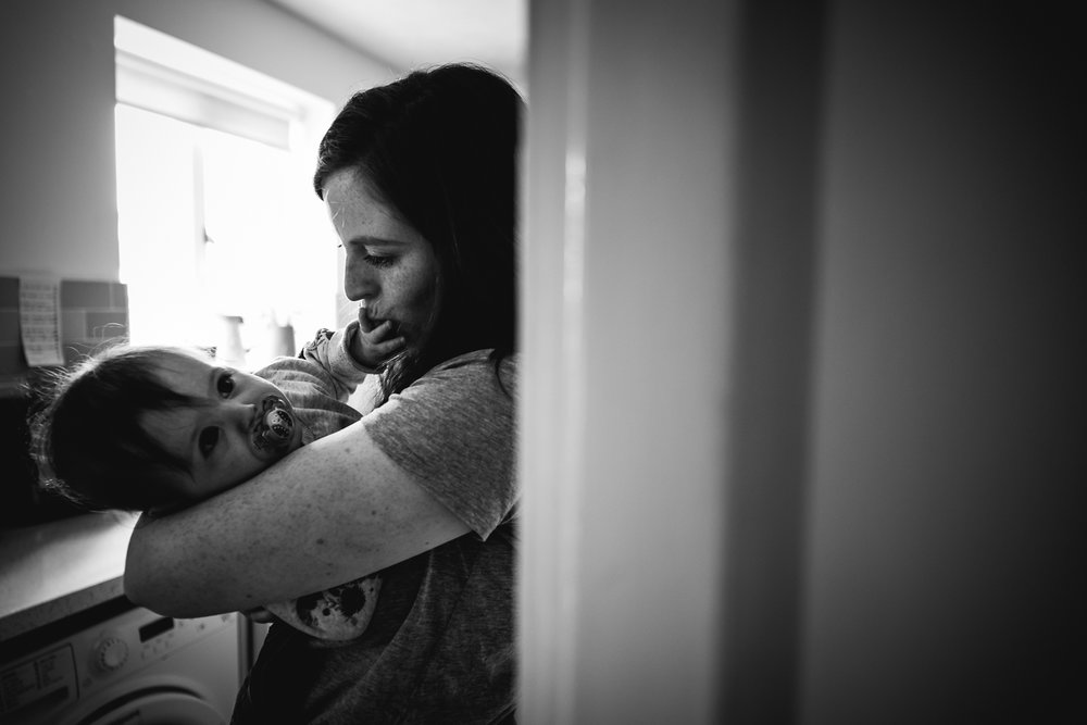 Baby's hand resting on mother's mouth in the doorway of the kitc