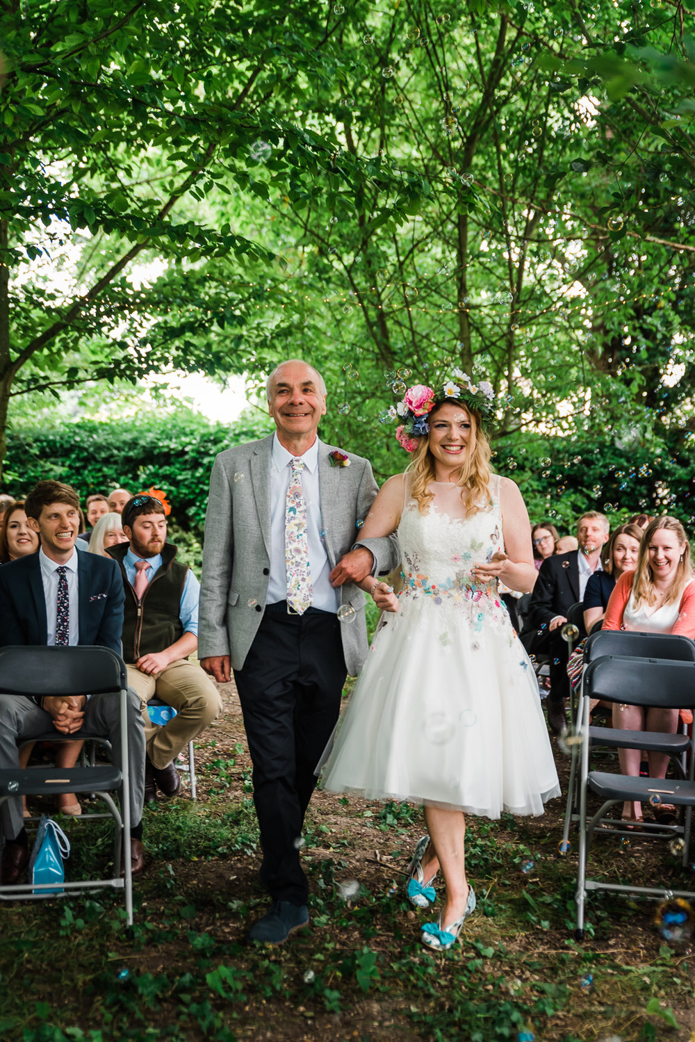 Father and bride walking arm-in-arm down the woodland path at he