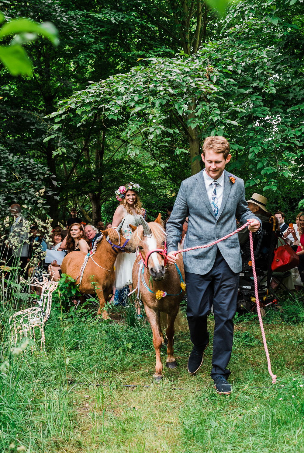 Bride and Groom with their unicorn ponies at their boho-themed w