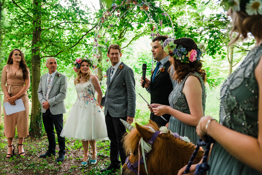 The wedding party standing in the woodland of the outdoor weddin