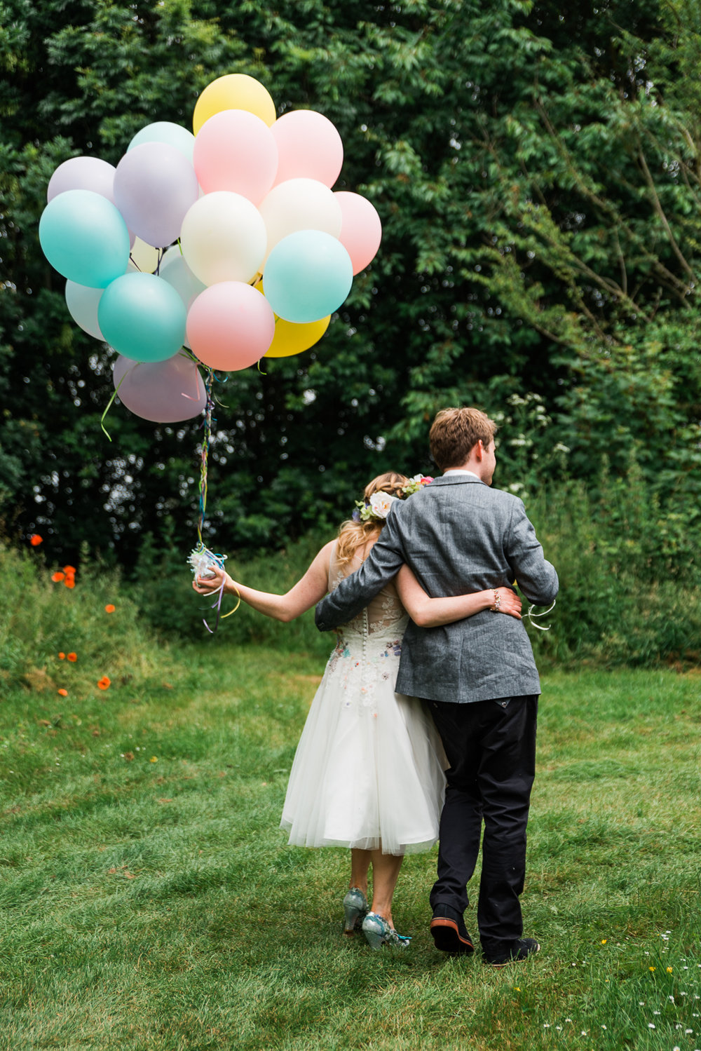 Wedding couple with colourful balloons at their festival-themed