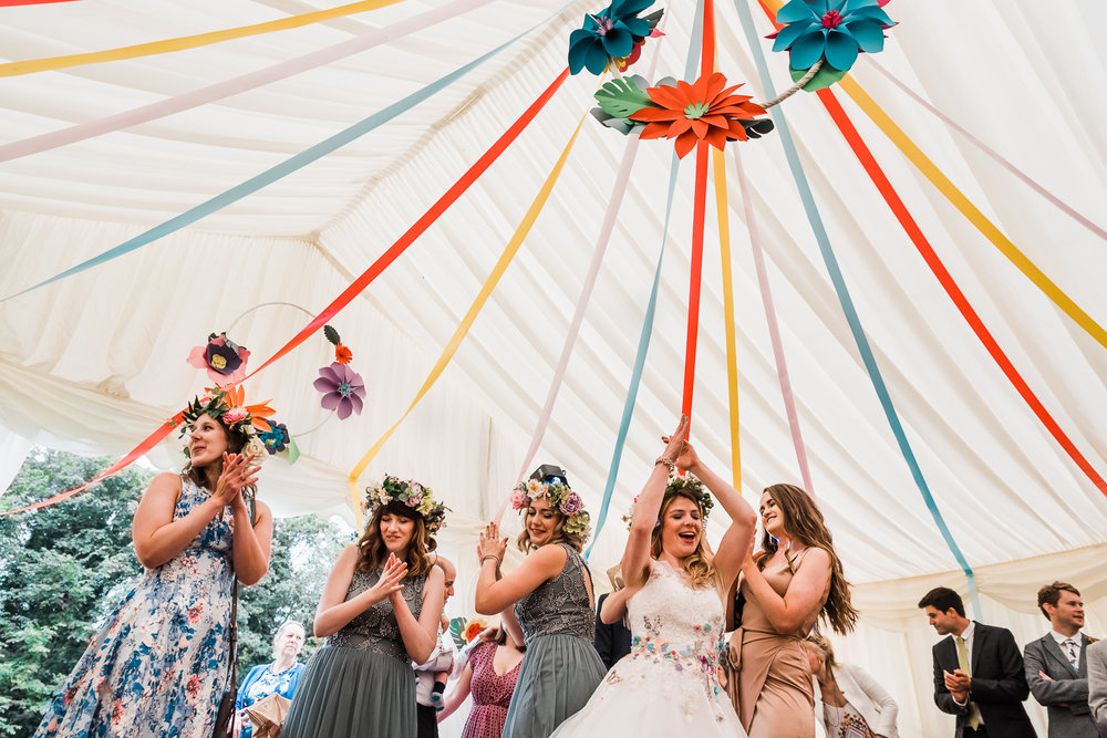 Bride and her bridesmaids dancing under a colourful marquee