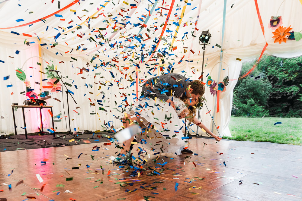Bride and groom on the dancefloor under a shower of colourful co