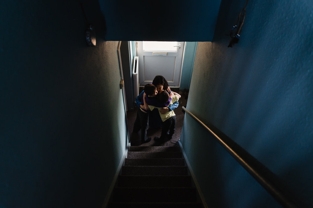 A mother gives her two children a hug in the hallway of the fami