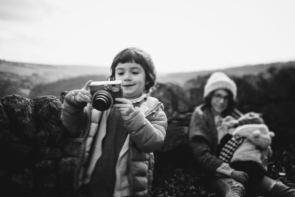 Copy of Black and white photograph of child holding onto an instamatix c