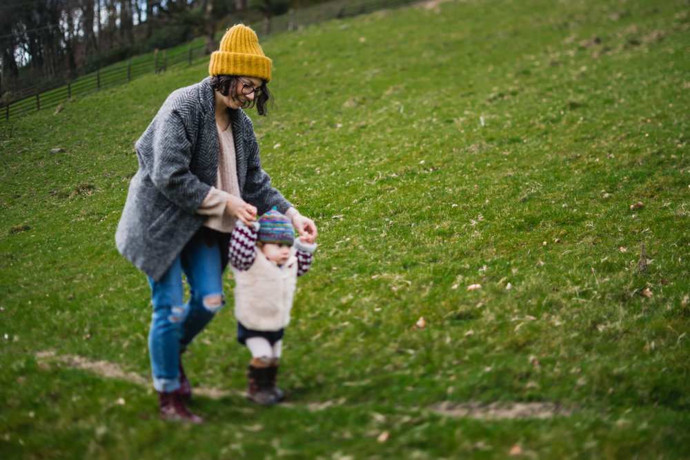 Copy of A mother walks with her toddler while holding onto her hand on t