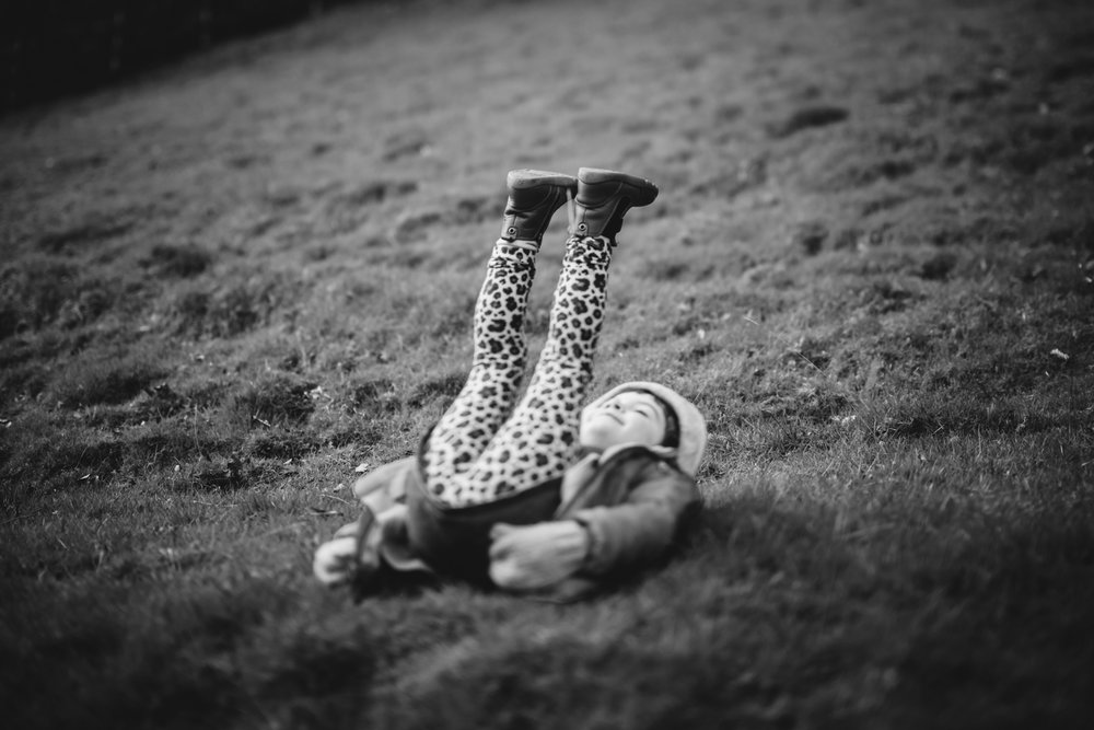 Copy of Black and white environmental portrait of a child lying on her b