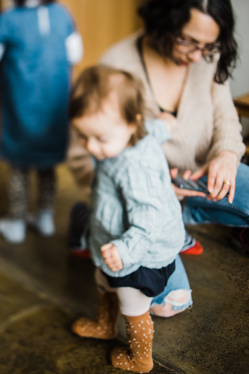 Copy of A toddler reaches for her mum's jumper