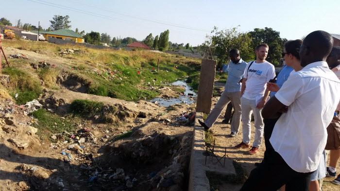 Petter med kollegor från WaterAid. Till vänster ser vi det planerade området där det byggs lyxvillor. Några meter till höger om bilden har vi det oplanerade slumområdet Ng'ombe där människor lever i misär.