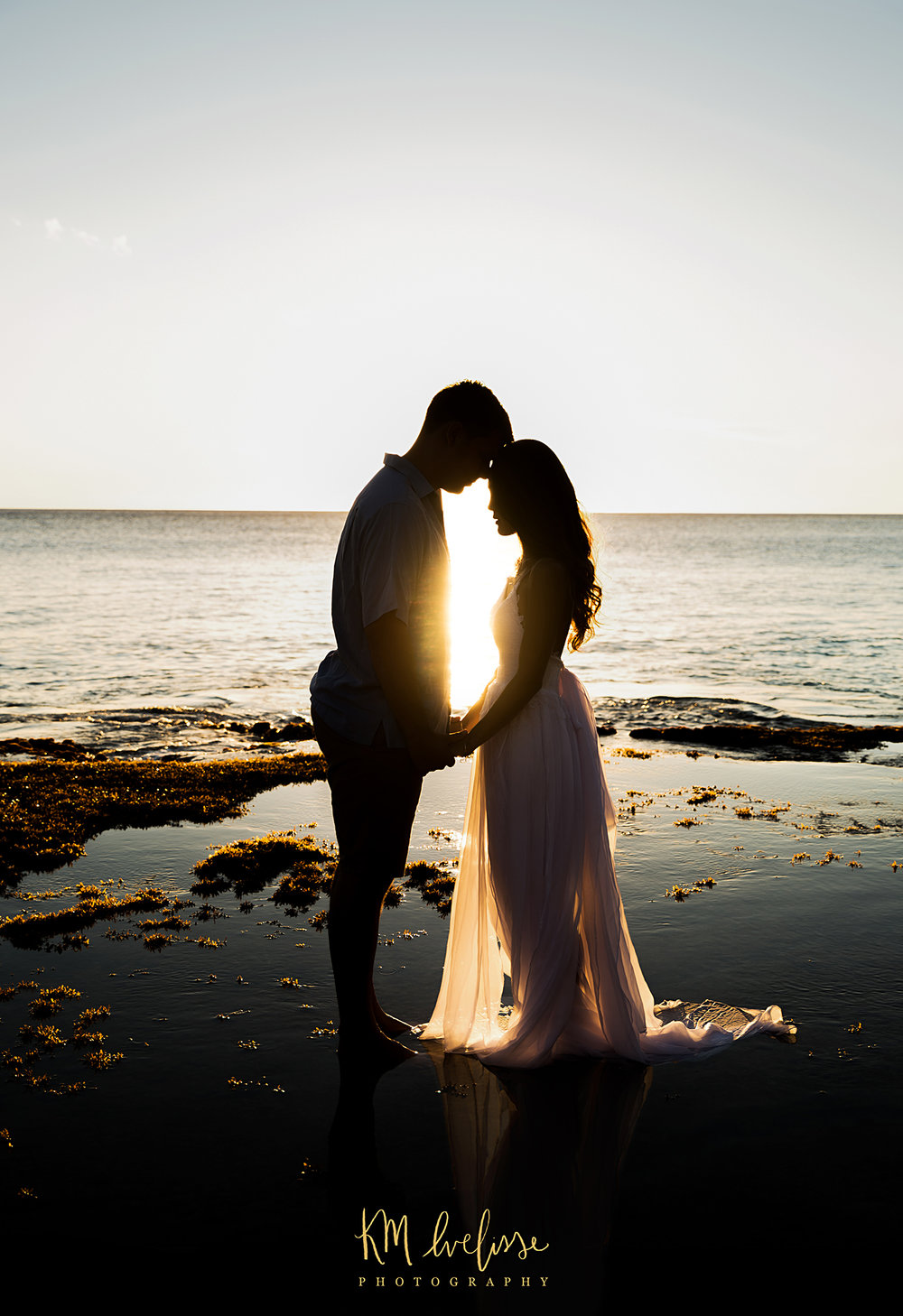 Silhouette shot at Makua Beach in Oahu Hawaii by KM Ivelisse Photography. This couples session was magical and the sunset did not disappoint.