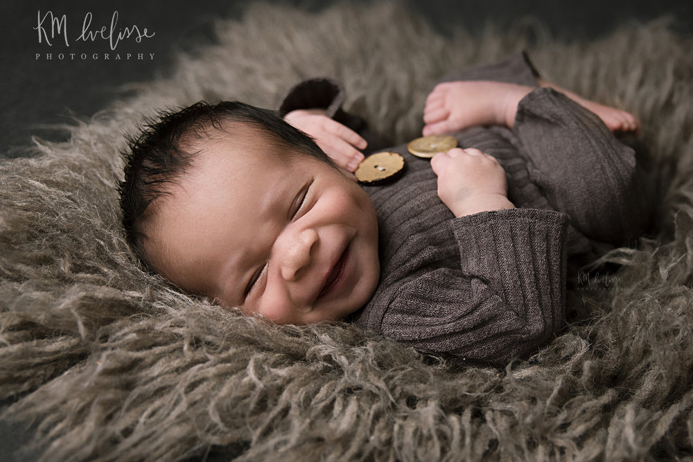 Studio session of a newborn boy on Oahu Hawaii. Wearing neutral colors and smiling newborn baby
