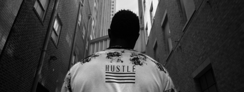 Man in alleyway wearing hustle jacket