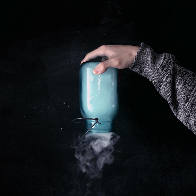 Hand holding jar filled with blue smoke upside down