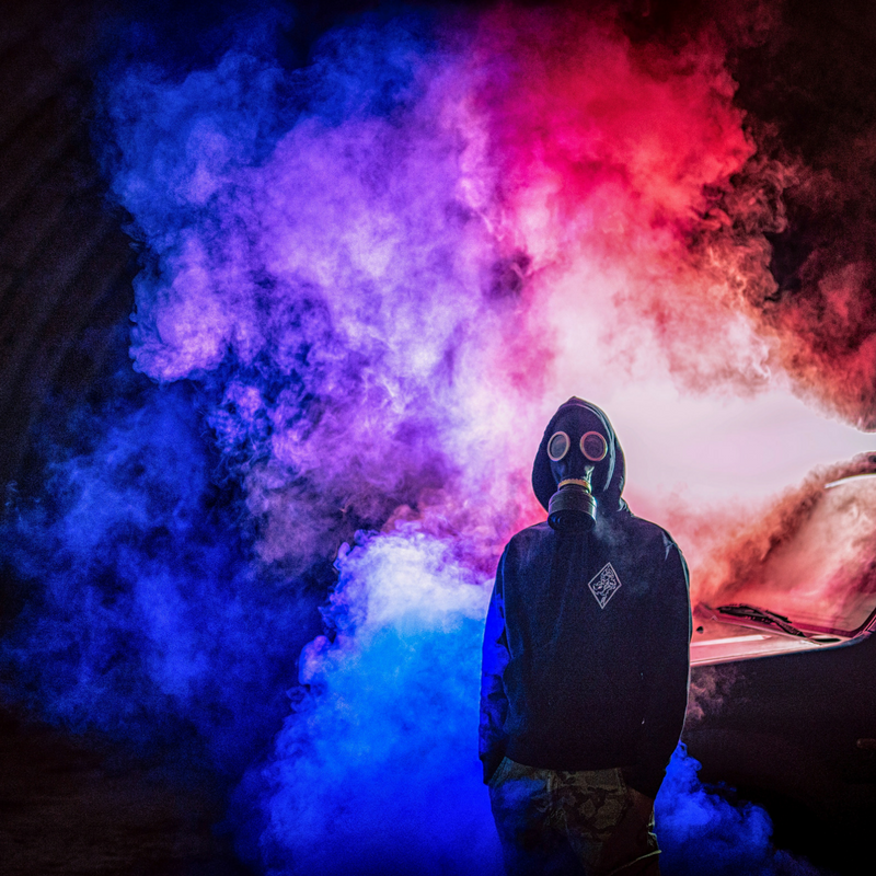 Man wearing gas mask in red and blue smoke