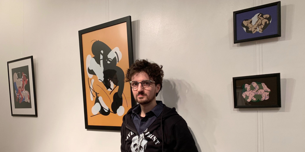 Tom White posing with four abstract NSFW artworks presented at the ARTificial visual arts exhibit