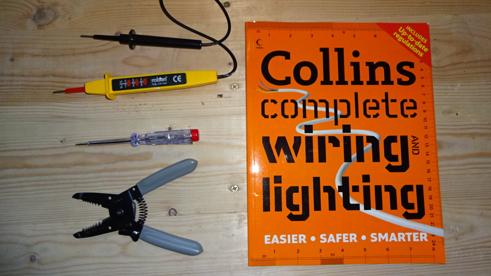 The tools from clockwise top:  Rolson mains-voltage tester ;  Collins complete wiring and lighting manual ;  Electric wire strippers/cutters; Neon 'electricians' screwdriver.