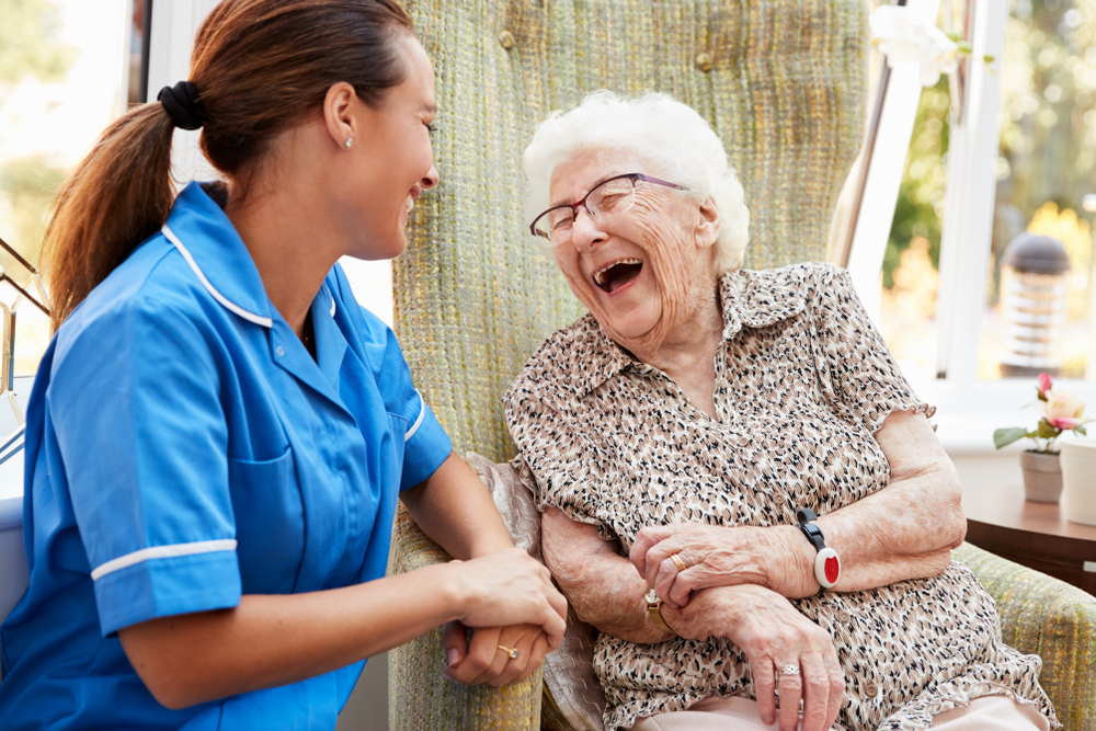 A nurse and an old aged woman laughing
