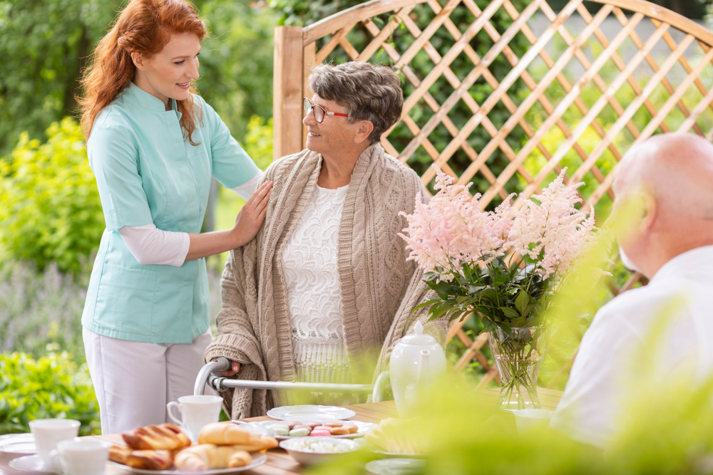 An old lady with caregiver at assisted living home