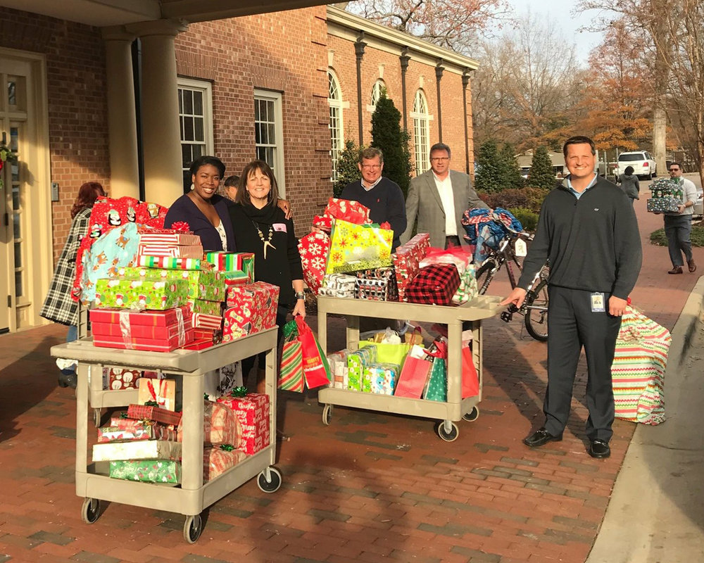 First National Bank employees pictured above help bring in donated presents to StepUp's Christmas party held on December 20, 2018, at our Alumni Program.