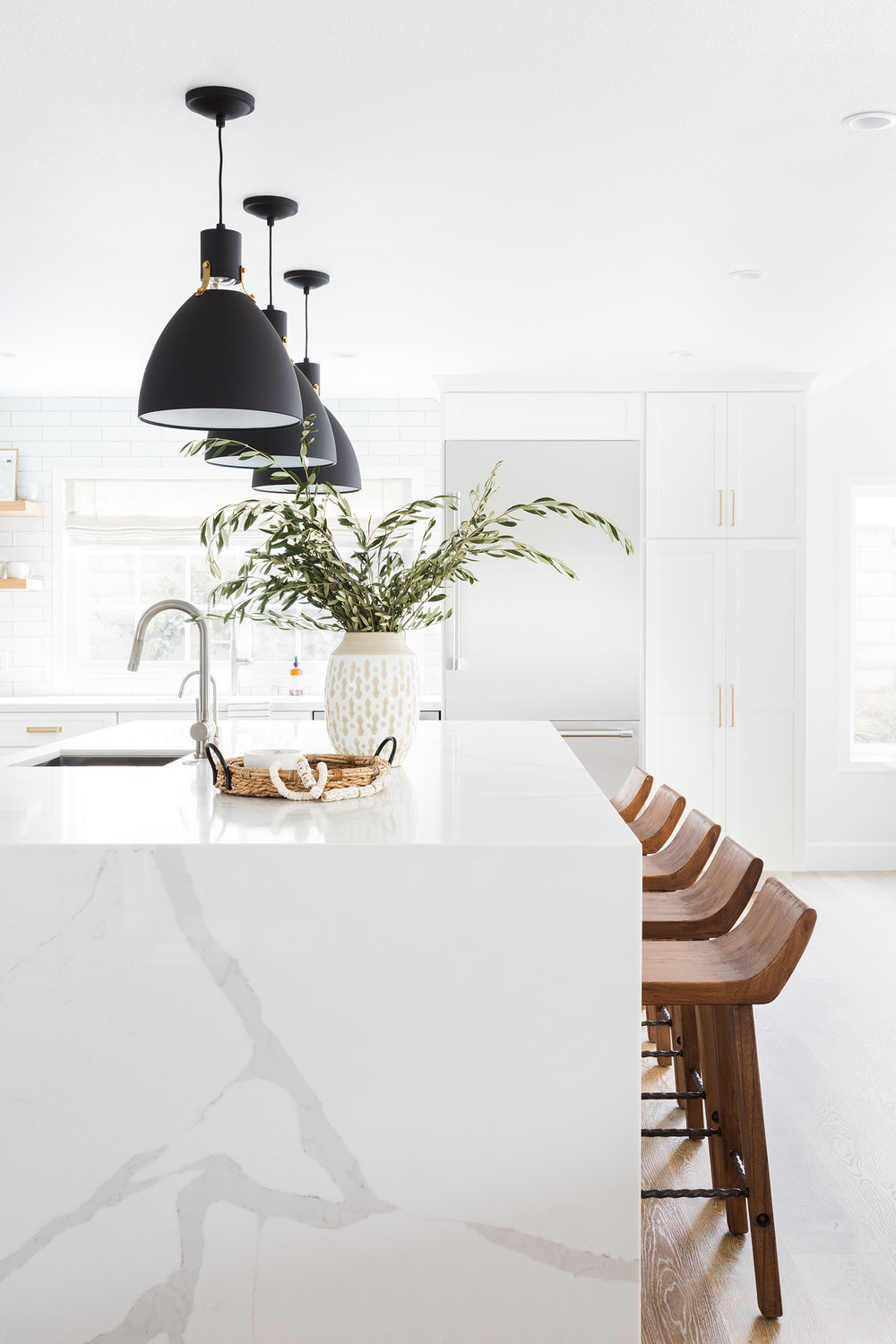Oak Hills Kitchen Remodel: Modern white kitchen with subway tile + statement lighting by Lindsey Brooke Design