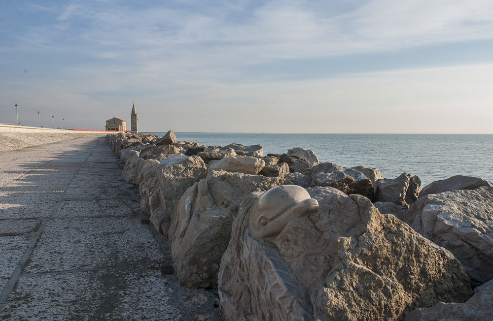 Lungomare Petronia with the Sanctuary of the Madonna dell'Angelo at the end and rock carvings on the breakwater