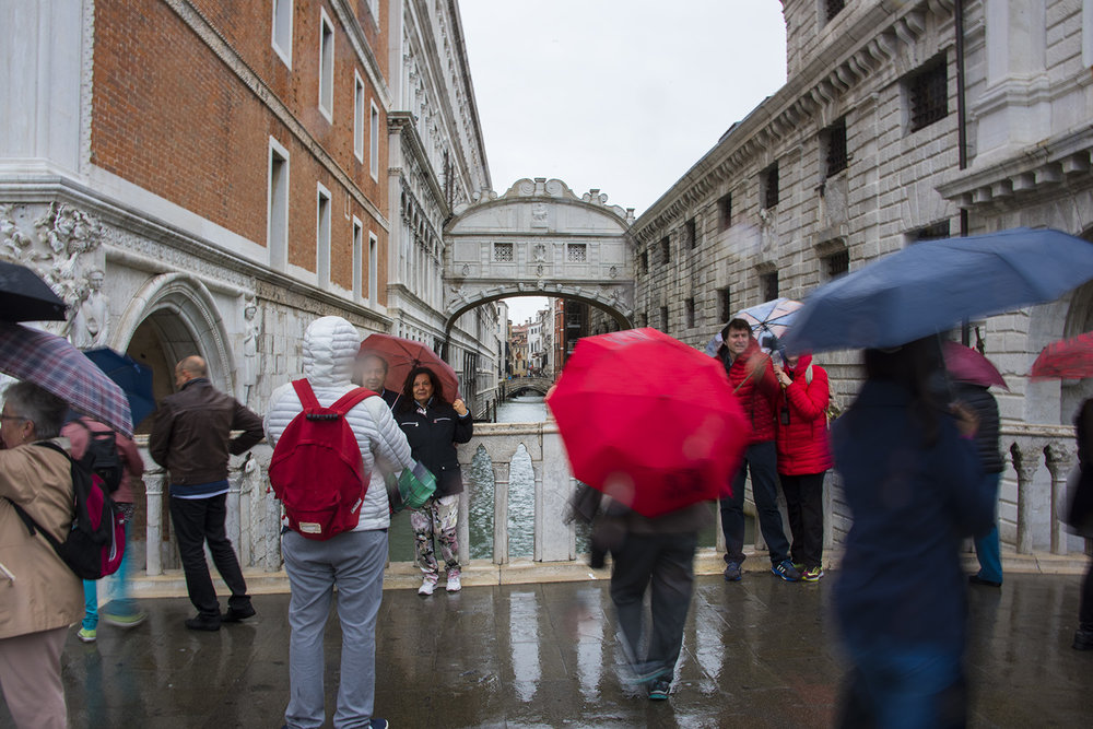 Tourists stopping for photos or selfies with the Bridge of Sighs in the background - in the rain
