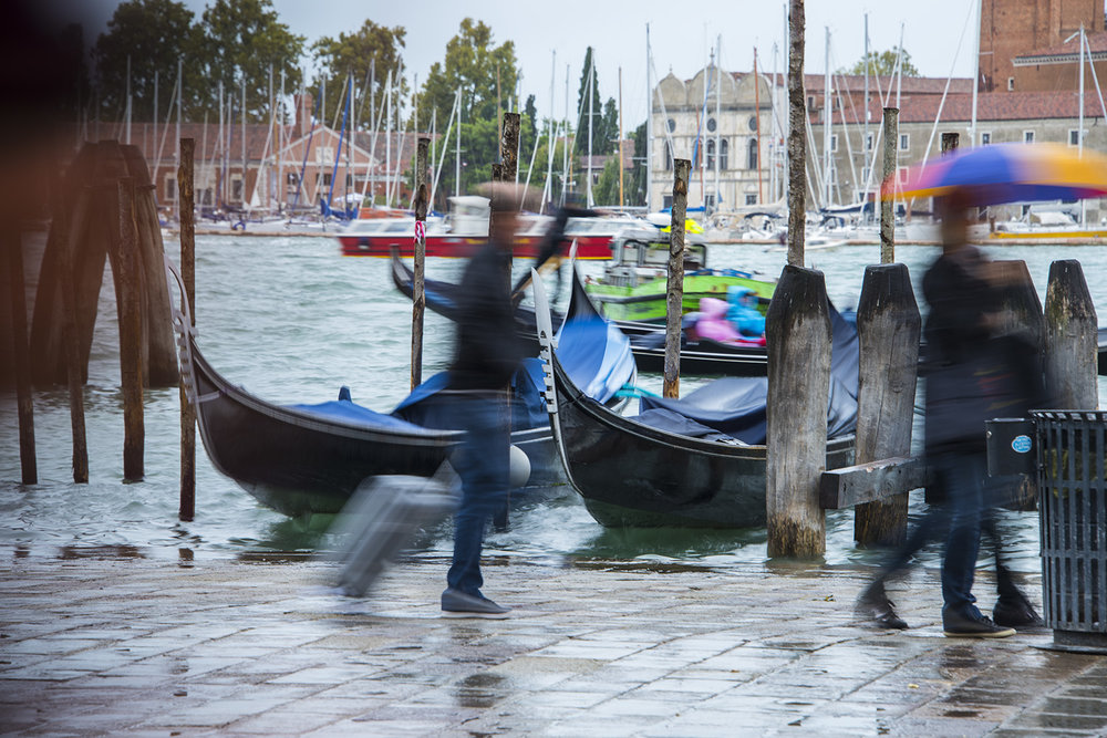 Tourists passing the gondolas moored on River deli Schiavoni - in the rain