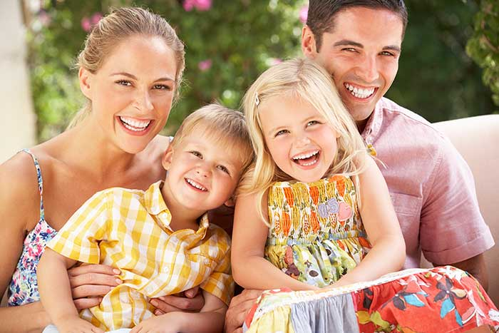A young family with healthy and white teeth smile for the camera.