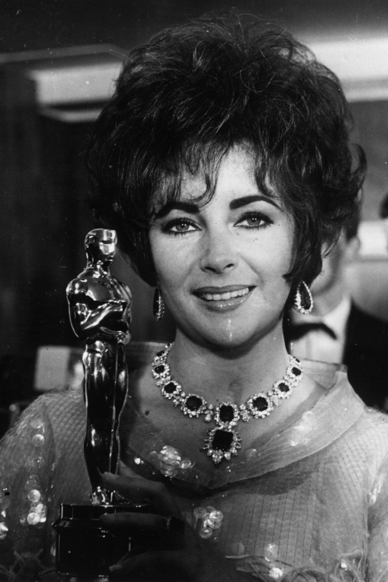 Elizabeth Taylor is wearing her custom made Emerald and Diamond Set by Bulgari