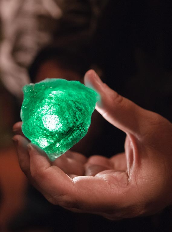 A hand-held flashlight reveals the green color of a rough emerald from the Coscuez Emerald mine in Columbia.