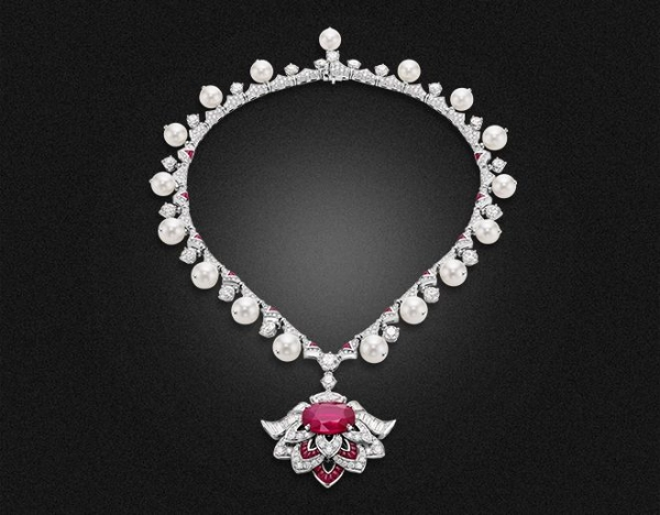 High Jewellery Necklace in platinum with 1 Mozambique oval ruby (12.10 ct), 2 round brilliant marquise diamonds (2.07), 17 Akoya cultures Pearls, 42 buff top Rubies (4.03 ct), 24 trapezoidal cut diamonds (2.98 ct), 20 round brilliant cut diamonds (10.37 ct) and pavé-set diamonds (7.54 ct).