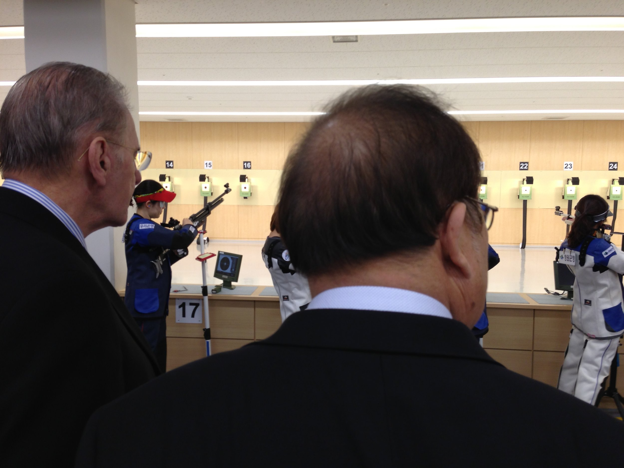 Jacques Rogge, the IOC president, left, watches Korean shooters practice at the Jincheon National Training Center