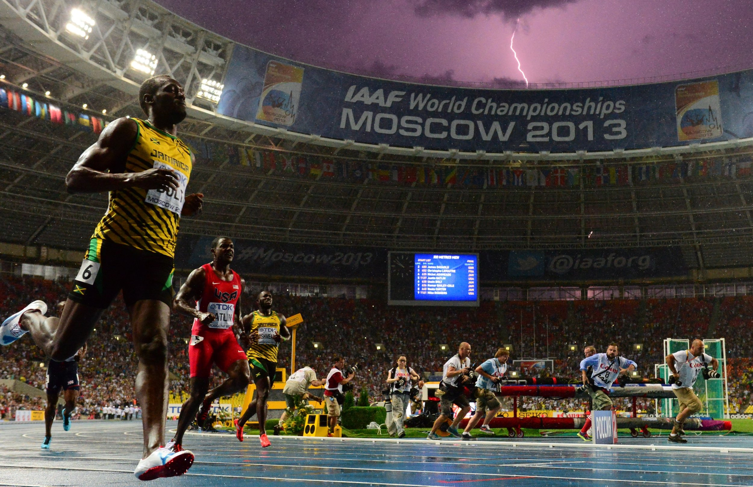 Usain Bolt winning the 2013 100 meters in Moscow as lightning flashes, Gatlin eight-hundredths of a second back // Getty Images