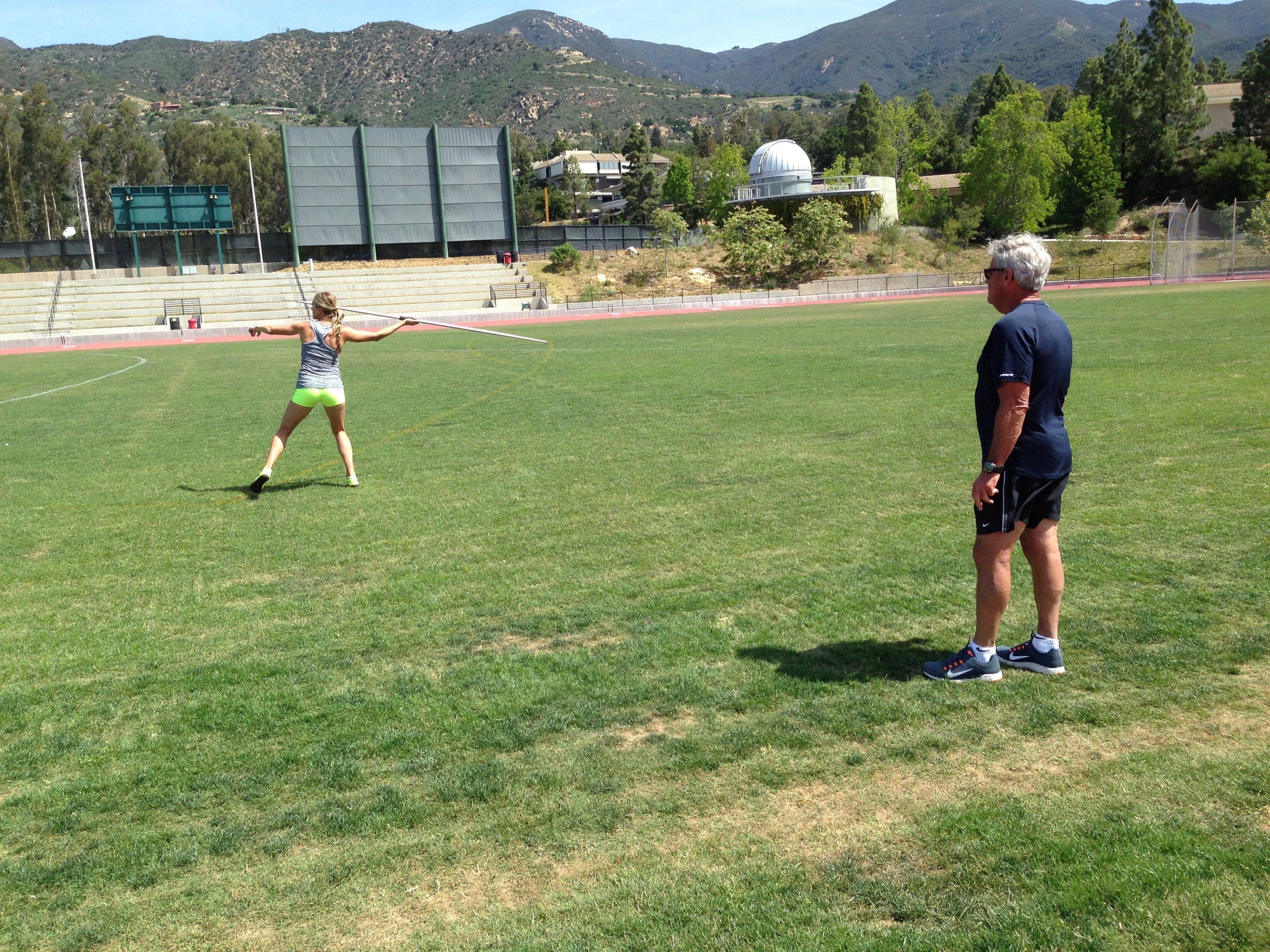 Coach Harry Marra watches as Brianne Theisen Eaton throws the javelin