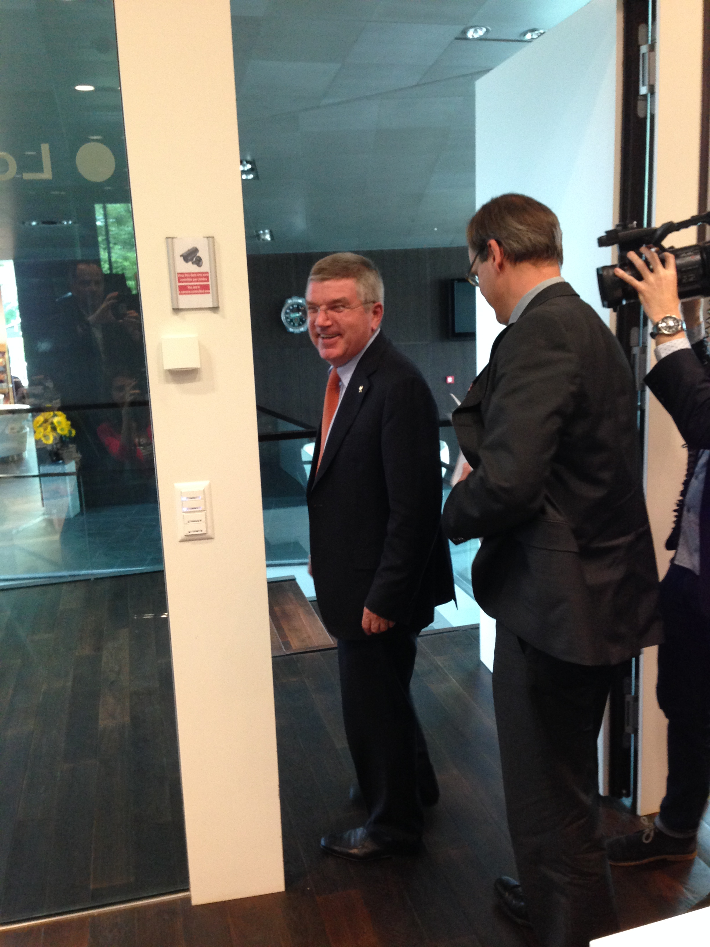 IOC president Thomas Bach, flanked by communications director Mark Adams, leaving Wednesday's news conference