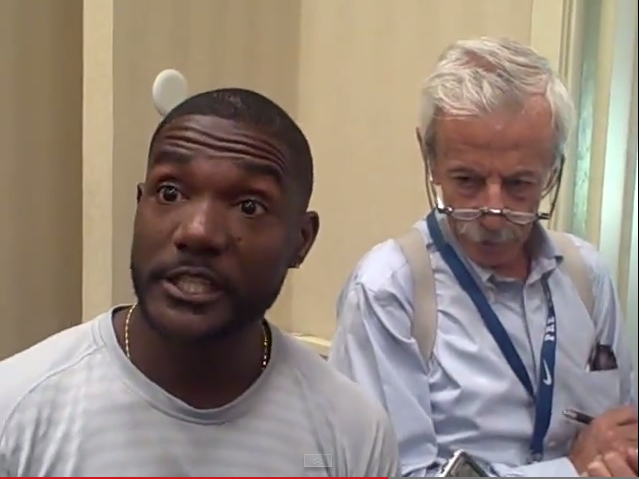 A screenshot of Gatlin at Friday's news conference. In the background is Franco Fava, a longtime Italian reporter // LetsRun.com