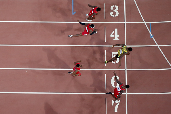 Usain Bolt crosses just ahead of a flailing Justin Gatlin // Getty Images
