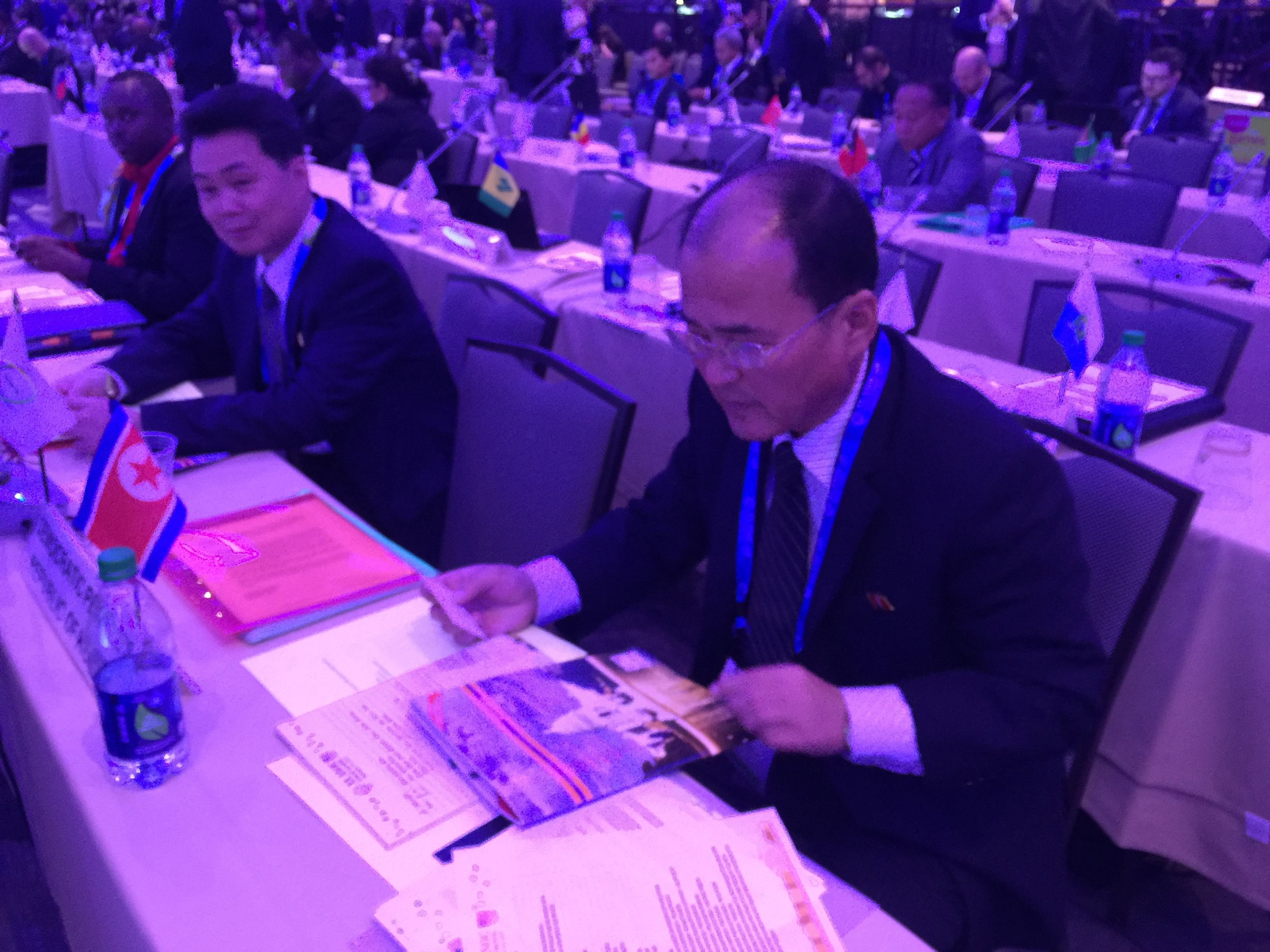 The North Korean delegation Thursday at ANOC, perusing the magazine from the Olympic publisher Around the Rings