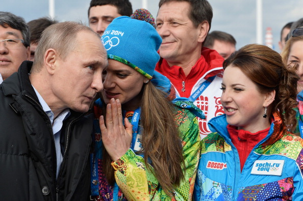 Russian president Vladimir Putin, left, listens in as Russian pole vault champion and Sochi 2014 Olympic village mayor Yelena Isinbayeva, center, whispers during a visit to the Olympic village at the 2014 Sochi Games // Getty Images