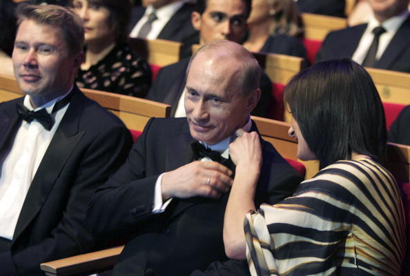 Isinbayeva, right, fixes Putin's collar at the 2008 Laureus awards. At left: Finnish former Formula One driver Mika Hakkonen // Getty Images