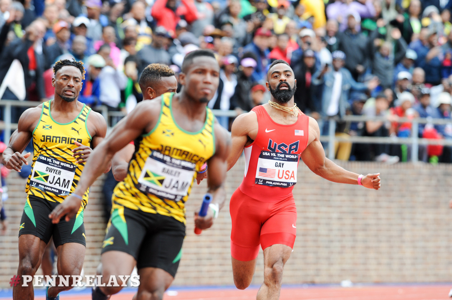 Tyson Gay, in red, struggles to hand off to Isiah Young at the 2016 Penn Relays // photo courtesy Penn Relays
