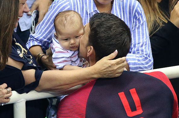 Gold medalist Michael Phelps kisses 3-month- old son Boomer after the 200 fly medal ceremony // Getty Images