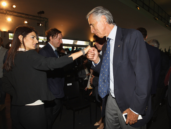 "Italian Olympic Committee president Giovanni Malago kisses Rome Mayor Virginia Raggi's hand at Euro 2020 event, Malago saying, ""I always do that with people I don't know that well"" // Getty Images"