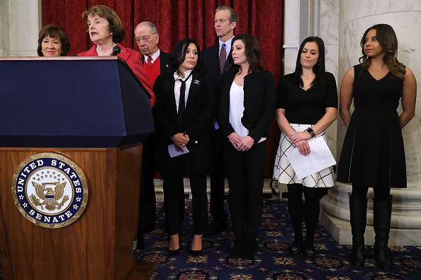 Sen. Susan Collins (R-Maine), Sen. Dianne Feinstein (D-Calif.), Senate Judiciary Committee Chairman Charles Grassley (R-Iowa) and Sen. John Thune (R-SD) join gymnasts Jeanette Antolin, Dominique Moceanu, Jamie Dantzscher and Mattie Larson at Tuesday's news conference Tuesday on Capitol Hill // Getty Images